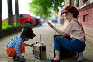 Imagen niños con radio en la acera.